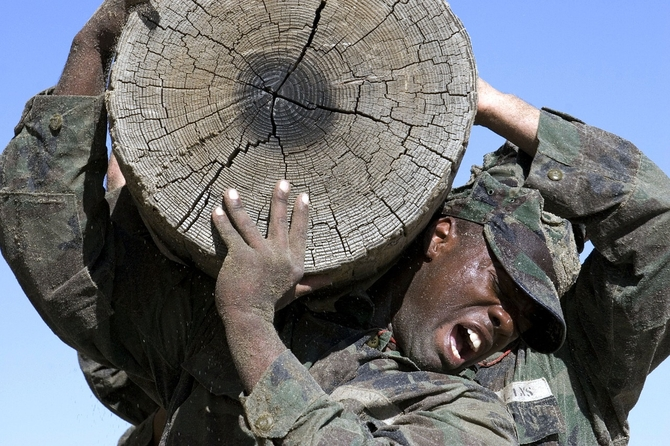 Navy SEALS training with a log
